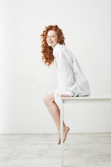 Śliczna piękna czuła kobieta z kręconymi rudymi włosami, śmiejąc się, pozowanie, siedząc na stole na białej ścianie