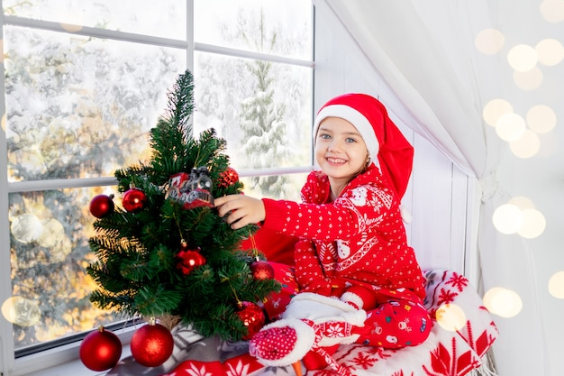 Śliczna piękna dziewczyna dziecko w oknie z choinką w czerwonym swetrze i kapeluszu na sylwestra lub boże narodzenie w domu i czeka na wakacje i prezenty