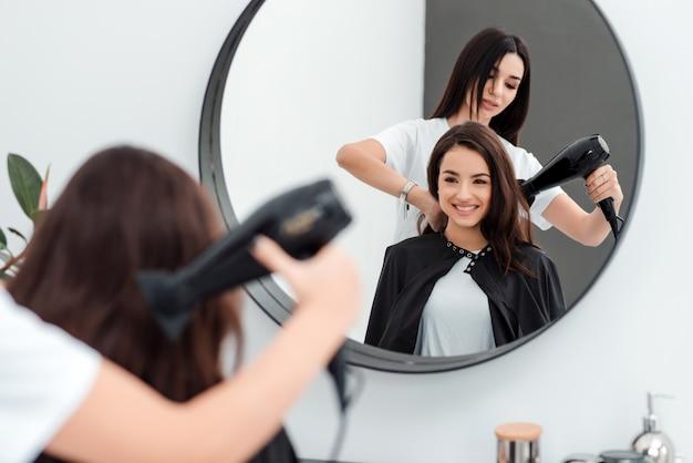 Śliczna piękna kobieta z długimi włosami patrzy w lustro, przyszła do salonu piękności, jej fryzjer pracuje z włosami
