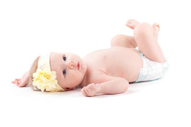 Śliczna piękna mała dziewczynka w białej pielusze i zawija kwiat