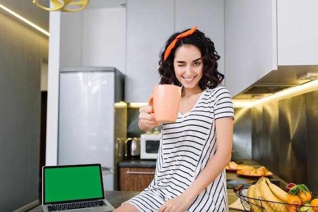 Śliczna piękna młoda kobieta z cięciem kręcone włosy, uśmiechając się z filiżanką herbaty w kuchni w nowoczesnym mieszkaniu. dzień dobry, komfort w domu, weekendy, dobra zabawa