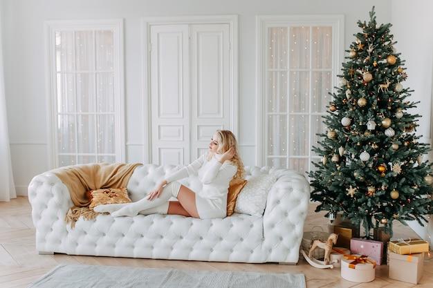 Śliczna piękna szczęśliwa młoda kobieta siedzi na białej kanapie obok choinki w jasnym wnętrzu przytulnego domu