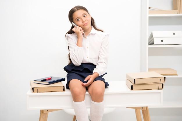 Śliczna plotkara. dzieciak rozmawia z przyjaciółmi. uczennica uśmiechnięta twarz omawia świeże plotki z kumplami. dziewczyna informująca rodziców oznaczyć szkołę. dziecko używa smartfona do komunikacji w szkole.