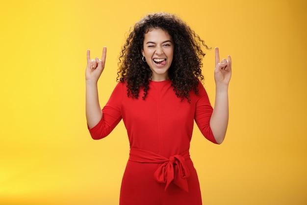 Śliczna, podekscytowana i odważna kobieta w wieku 25 lat, wystawiająca język, jak wygłupia się, bawiąc się na koncercie, mrugając radośnie i pokazując rock-n-rollowy gest, czując się rozbawiona i żywa na żółtym tle.