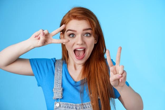 Śliczna podekscytowana rudowłosa entuzjastyczna dziewczyna uśmiecha się, wygląda radośnie pokaż pokój, znaki zwycięstwa w pobliżu twarzy, optymistyczna szczęśliwa postawa, uwierz w wygraną, stań na niebieskim tle pozytywnie, dobrze się bawiąc ciesz się wakacjami