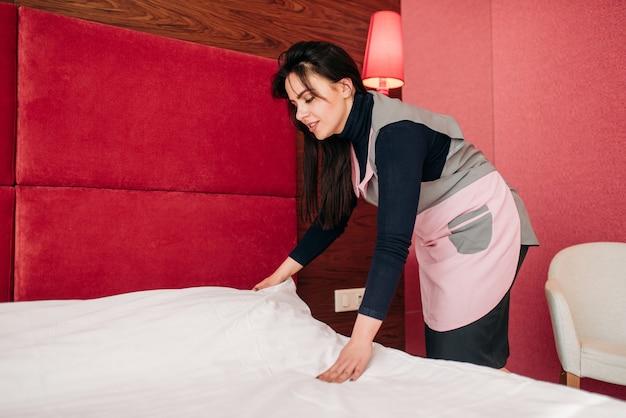 Śliczna pokojówka ścieli łóżko w pokoju hotelowym