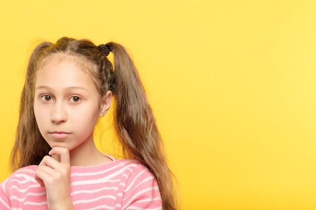 Śliczna poważna dorastająca dziewczyna z portretem ogony świń na żółto.