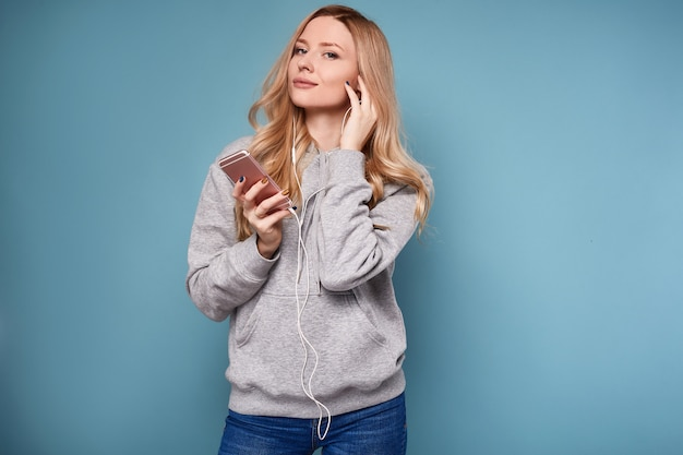 Śliczna pozytywna blondynki kobieta słucha muzykę w bluza z kapturem