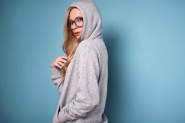 Śliczna pozytywna blondynki kobieta w szarej bluzie i szkłach