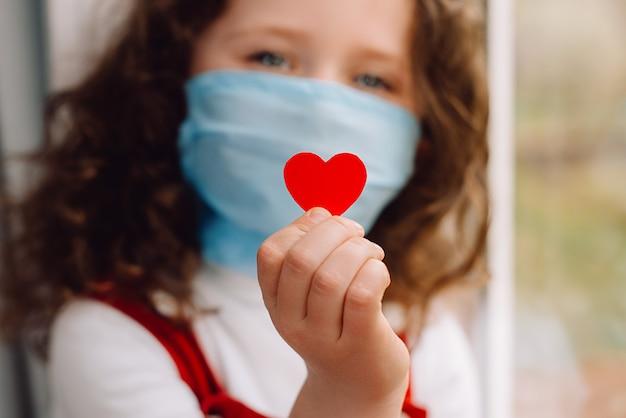 Śliczna przedszkolak w ochronnych maskach medycznych siedzi na parapecie, trzymając czerwone serce, aby okazać uznanie i podziękować wszystkim niezbędnym pracownikom podczas pandemii covid-19. selektywne ustawianie ostrości
