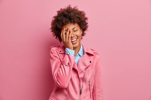 Śliczna, przejęta młoda afro amerykanka robi dłoń na twarzy i radośnie się śmieje, wyrażając pozytywne emocje