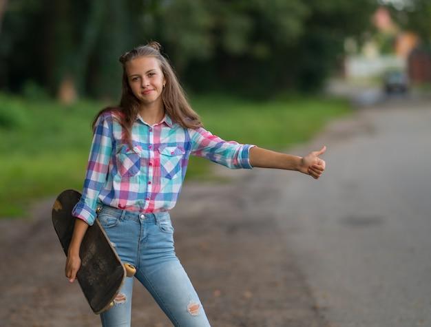 Śliczna przyjazna młoda kobieta z deskorolką pod pachą, stojąca na poboczu drogi, kciuki do windy