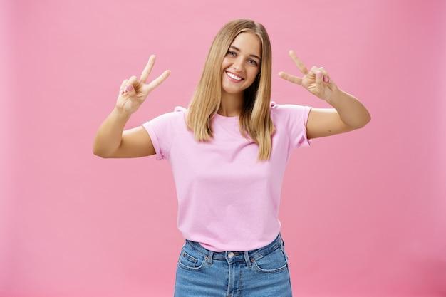 Śliczna Pulchna, Beztroska Młoda Kobieta Z Krótkimi Jasnymi Włosami, Przechylającą Głową, Pokazująca Gesty Pokoju Na Różowym Tle. Skopiuj Miejsce Premium Zdjęcia