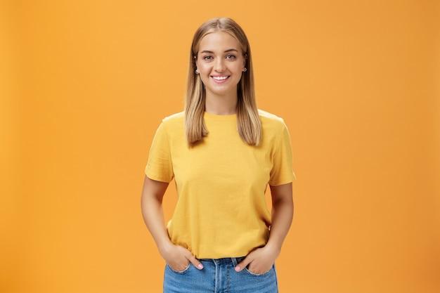 Śliczna pulchna kobieta o opalonej skórze i jasnych włosach pozuje optymistycznie i radośnie na pomarańczowym tle trzymając się za ręce w kieszeniach uśmiechając się szeroko do aparatu charyzmatyczna i sympatyczna