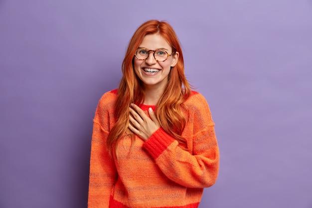 Śliczna radosna kobieta czuje wdzięczność za słuchanie miłego komplementu, szeroko uśmiechniętego uśmiechu wygląda radośnie ubrana w swobodny sweter.