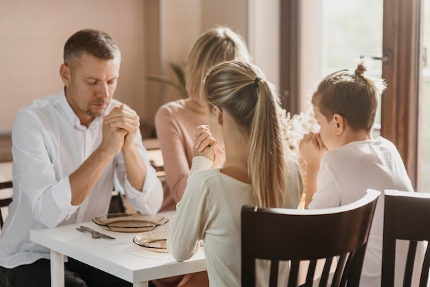 Śliczna rodzina modląca się razem przed jedzeniem