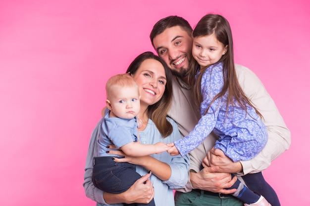 Śliczna rodzina pozowanie i uśmiecha się do kamery razem na różowym tle