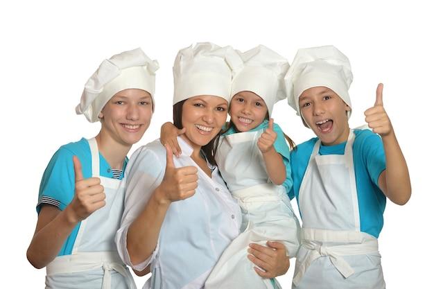 Śliczna rodzina pozuje w mundurach szefa kuchni na białym tle