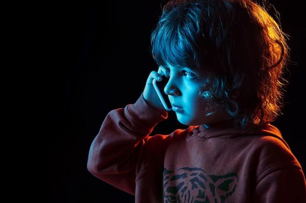 Śliczna rozmowa przez telefon. ścieśniać. portret kaukaski chłopca na ciemnej ścianie w świetle neonu. piękny model z kręconymi włosami. pojęcie ludzkich emocji, wyraz twarzy, sprzedaż, reklama, nowoczesne technologie, gadżety.