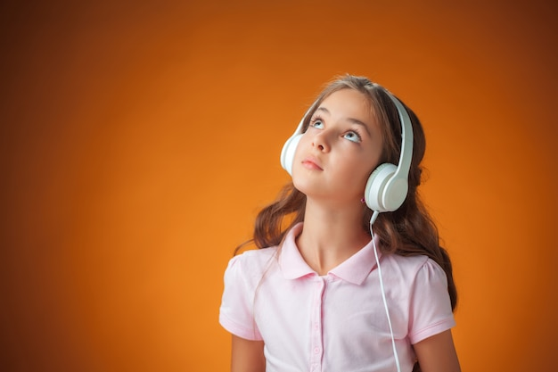 Śliczna rozochocona mała dziewczynka na pomarańcze ścianie