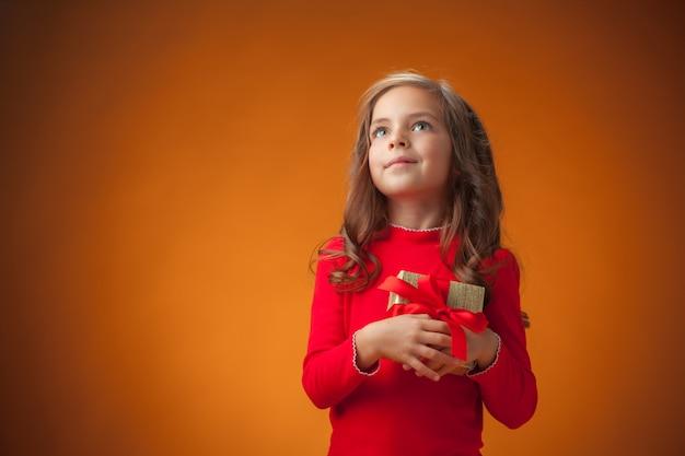 Śliczna rozochocona mała dziewczynka na pomarańczowym tle