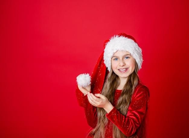 Śliczna rozochocona mała dziewczynka w święty mikołaj kapeluszu na czerwieni