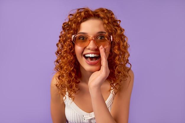 Śliczna ruda dziewczyna z lokami w okularach przeciwsłonecznych zakryła usta dłonią i opowiada plotki na fioletowej ścianie.