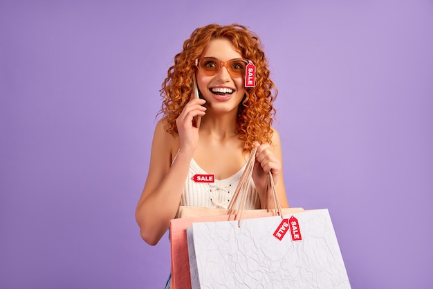 Śliczna rudowłosa dziewczyna z lokami i etykietami sprzedaży rozmawia przez telefon na fioletowym tle