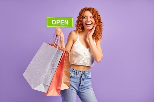 Śliczna rudowłosa dziewczyna z lokami i torbami na zakupy, trzymająca znak z napisem otwartym na fioletowym tle