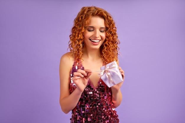 Śliczna rudowłosa dziewczyna z lokami w błyszczącej sukience otwiera prezent na fioletowym tle