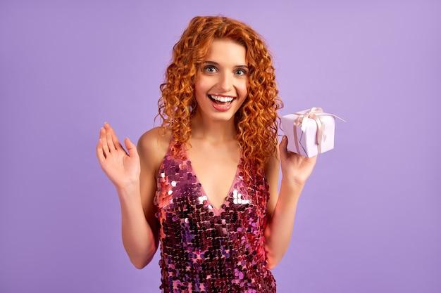 Śliczna rudowłosa dziewczyna z lokami w błyszczącej sukience trzyma prezent na fioletowym tle