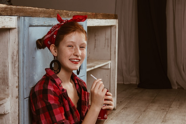 Śliczna rudowłosa dziewczyna z piegami, ubrana w czerwoną chustkę i kraciastą koszulę i pijąca napój bezalkoholowy