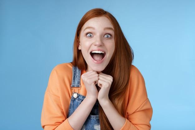 Śliczna rudowłosa europejska dziewczyna niebieskie oczy reaguje piegi rozbawiona szokująca plotka unieść brwi opadająca szczęka zaskoczony uśmiechnięty podekscytowany odebrać rolę teatralną radość zdumiony niebieskie tło
