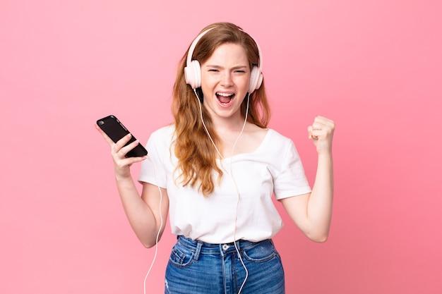 Śliczna rudowłosa kobieta krzycząca agresywnie ze złym wyrazem twarzy ze słuchawkami i smartfonem