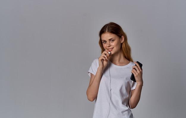 Śliczna rudowłosa kobieta w koszulce i słuchawkach