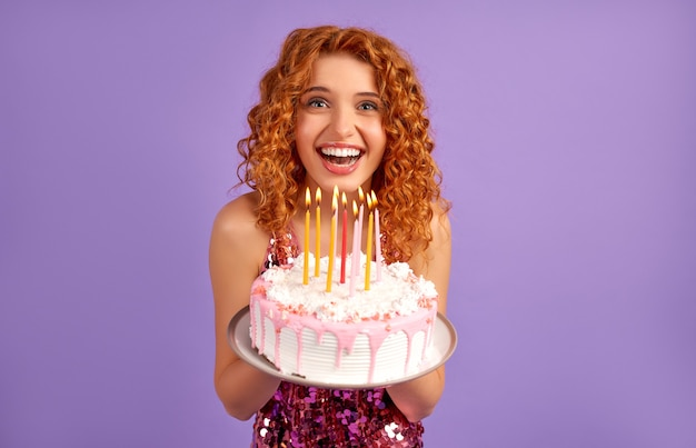 Śliczna rudowłosa kobieta z lokami w błyszczącej sukience trzyma ciasto ze świeczkami na fioletowym tle