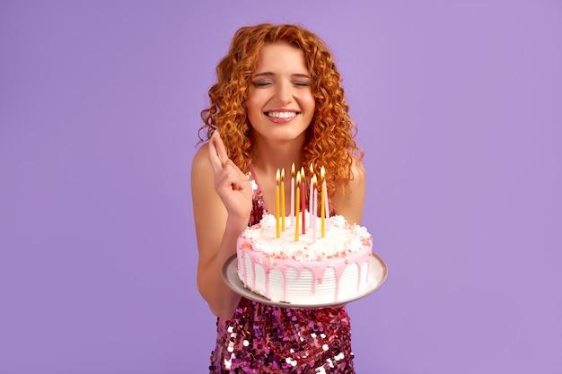 Śliczna rudowłosa kobieta z lokami w błyszczącej sukience trzymająca ciasto ze świecami, zamkniętymi oczami i skrzyżowanymi palcami, odizolowana na fioletowo