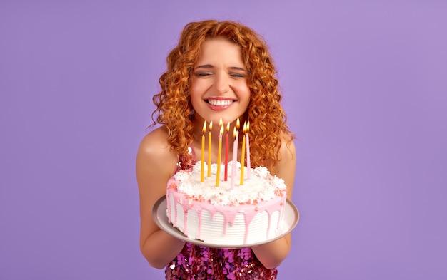 Śliczna rudowłosa kobieta z lokami w błyszczącej sukience trzymająca tort ze świecami, zamykająca oczy odizolowane na fioletowo