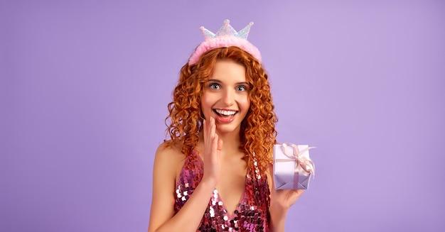 Śliczna rudowłosa księżniczka z lokami w błyszczącej sukience i koroną na głowie trzymająca prezent na fioletowym tle