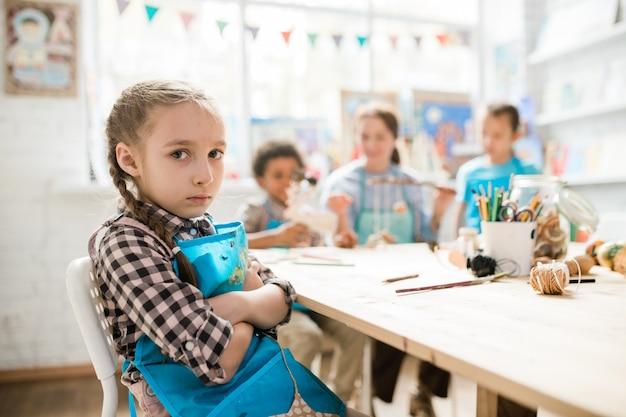 Śliczna samotna dziewczyna w fartuchu, patrząc na ciebie, siedząc na tle swoich kolegów z klasy i nauczyciela w klasie