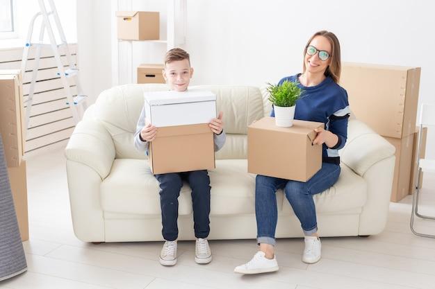 Śliczna samotna mama i synek sortują pudełka z rzeczami po przeprowadzce. pojęcie