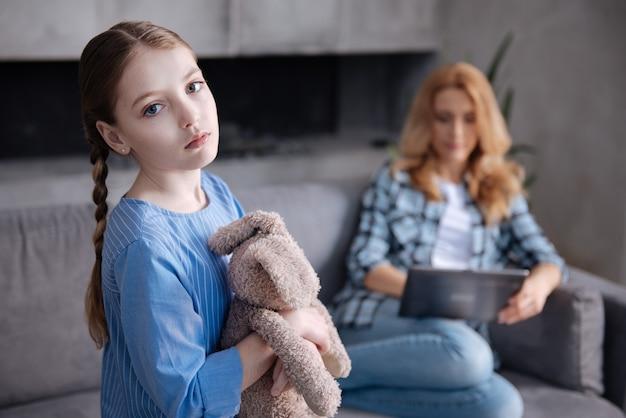 Śliczna samotna rozczarowana dziewczyna czeka na miłość rodzica w domu i przytula puszystą zabawkę, podczas gdy mama surfuje po internecie