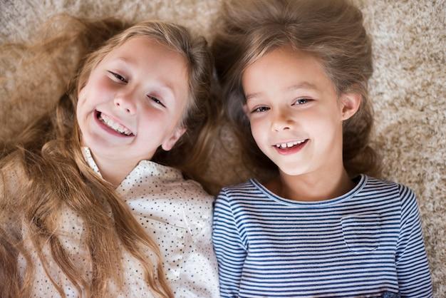 Śliczna siostra bawi się na puszystym dywanie