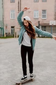 Śliczna skater dziewczyna i jej deskorolka