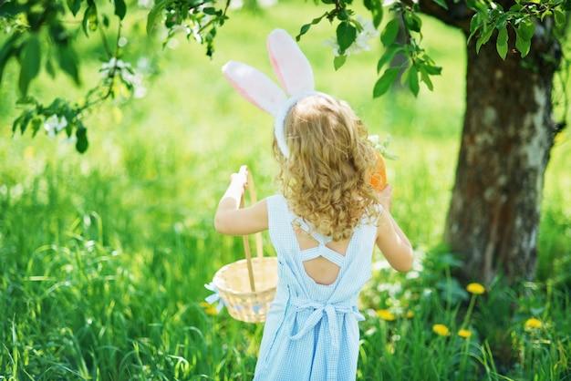 Śliczna śmieszna dziewczyna z wielkanocnymi jajkami i królików ucho przy ogródem. koncepcja wielkanocy. śmiech dziecka na polowanie na pisanki