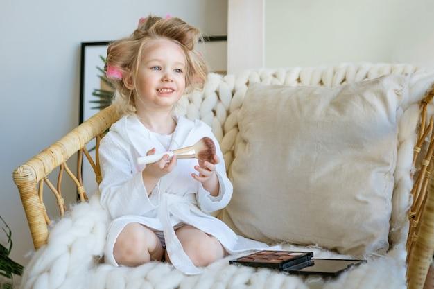 Śliczna śmieszna mała dziewczynka z lokówek na głowie siedzi na krześle i robi makijaż pędzlem, grając wizażystę