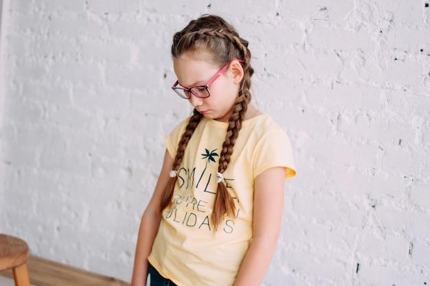 Śliczna smutna nastolatka dziewczyna w szkłach z długie włosy odosobnionym na białym ściana z cegieł