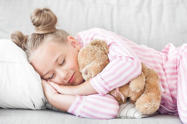 Śliczna śpiąca dziewczyna w łóżku
