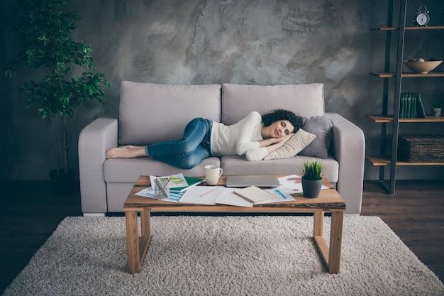 Śliczna spokojna śpiąca spokojna dziewczyna leżąca na kanapie odpoczynku w nowoczesnym loftowym stylu industrialnym