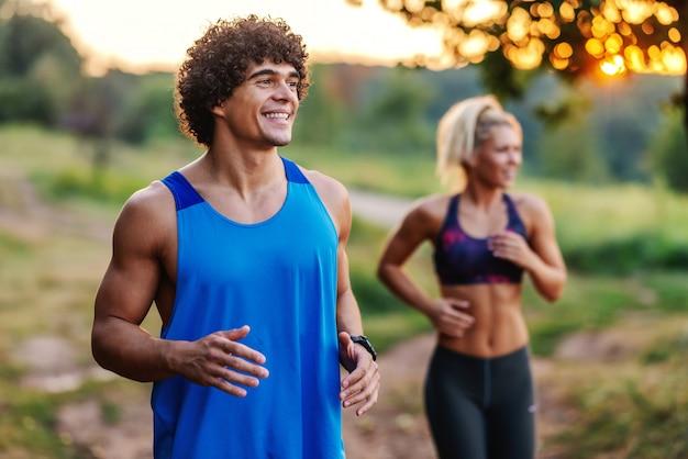 Śliczna sporty para biega w naturze w pogodnym letnim dniu.